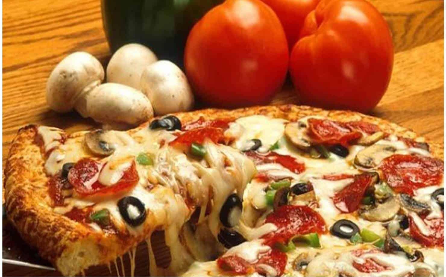 Pizza na Mesa com Tomates ao fundo