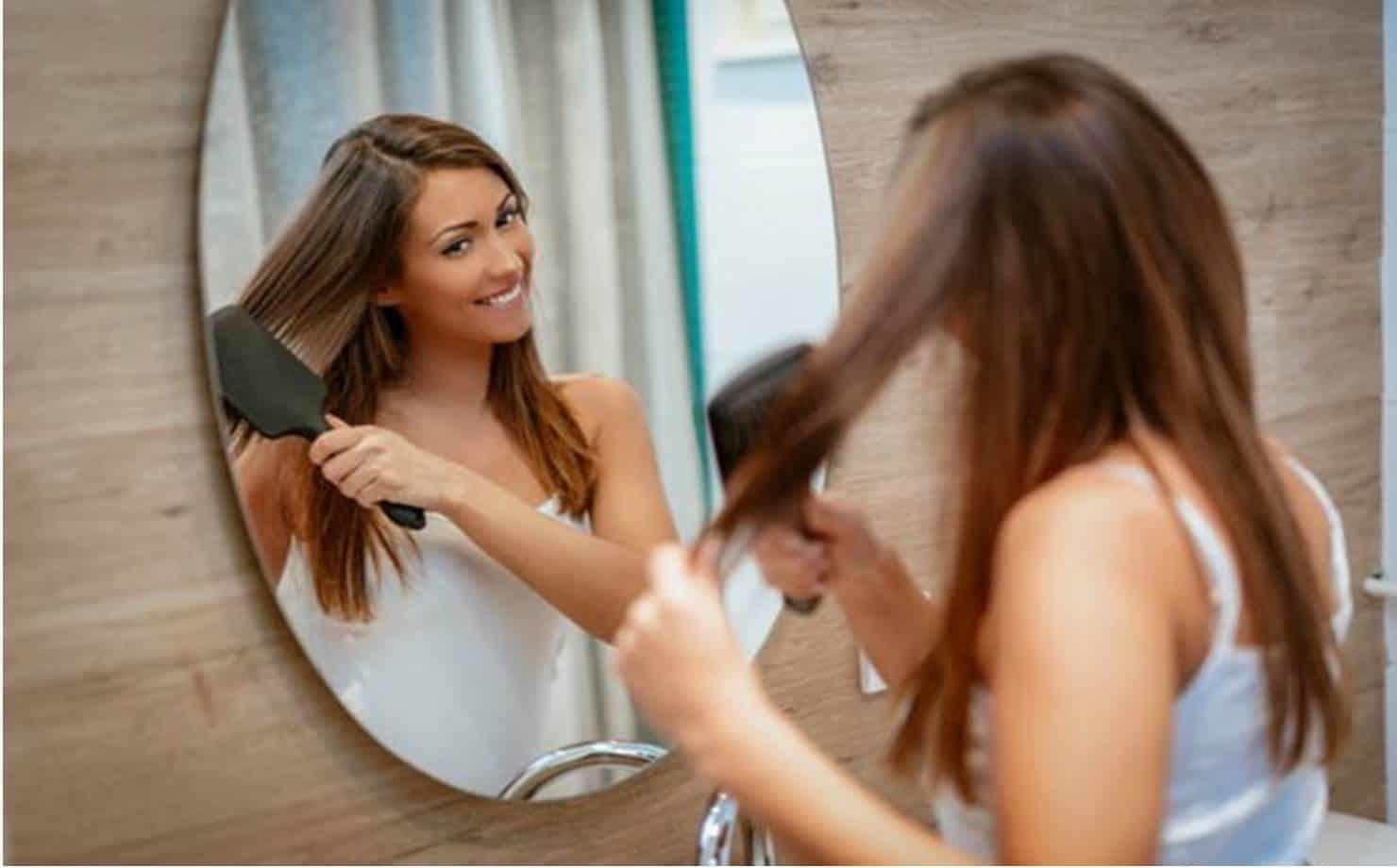 Mulher Penteando o Cabelo na Frente do Espelho